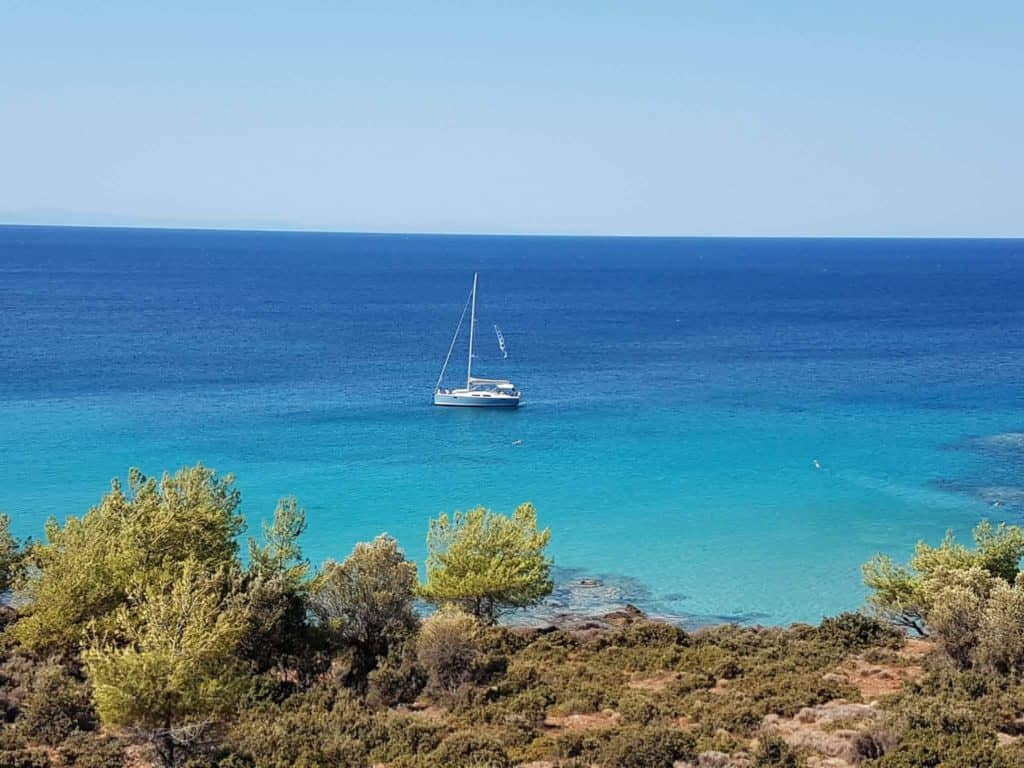 Aeolus yacht at Notos beach blue sky and emerald waters