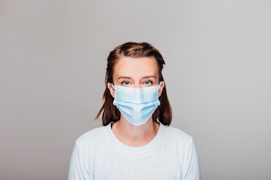 woman-in-grey-sweater-wearing-disposable-face-mask